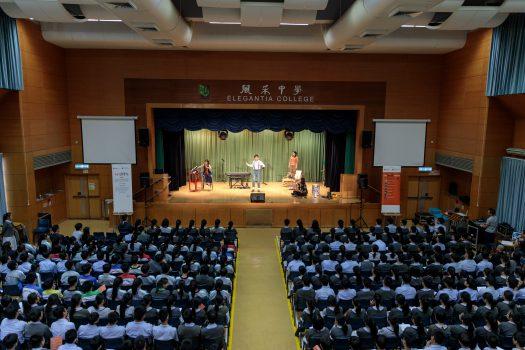 從遠處拍下整個學校禮台,台上藝術家在表演,台下學生專心欣賞