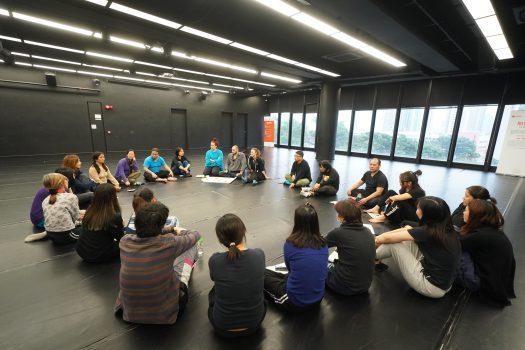 二十名參加者圍大圈坐在地上,與三名海外導師在討論。